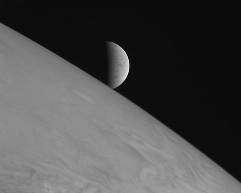 image of Europa rising over the limb of Jupiter